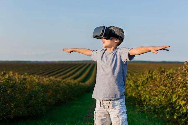 Charmant petit garçon s'amuse avec des lunettes de réalité virtuelle Photo gratuit