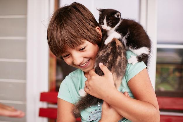 Charmant petit garçon tient deux minous dans ses bras Photo gratuit