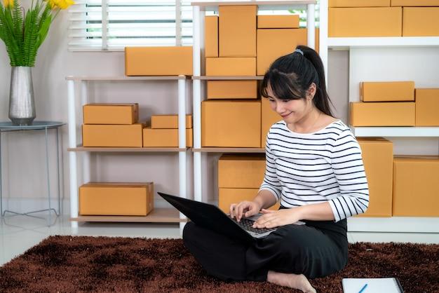 Charmante belle adolescente asiatique propriétaire femme d'affaires travaille assis sur le sol pour les achats en ligne, à la recherche de l'ordre dans un ordinateur portable avec du matériel de bureau, concept de style de vie d'entrepreneur Photo Premium
