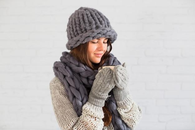 Charmante dame en mitaines, bonnet et écharpe avec une tasse dans les mains Photo gratuit