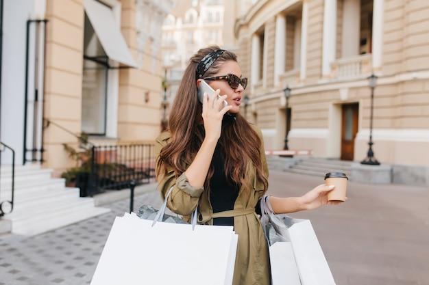 Charmante Femme D'affaires Parlant Au Téléphone Tout En Faisant Du Shopping Photo gratuit