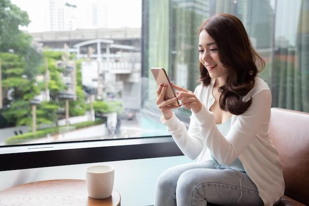 Charmante Femme Asiatique Sourire Lecture De Bonnes Nouvelles Sur Téléphone Mobile Pendant Le Repos Dans Un Café Photo Premium