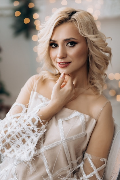 Charmante femme blonde en robe blanche pose dans une pièce avec un grand sapin de noël Photo gratuit
