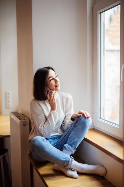 Charmante Femme Dans La Chambre Assise Près De La Fenêtre Dans Des Vêtements Décontractés Pull Blanc Photo gratuit
