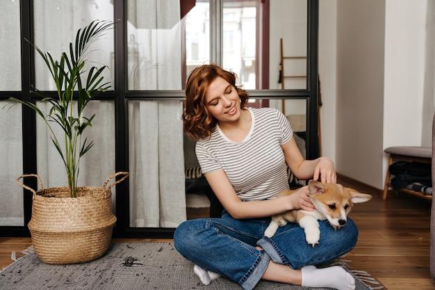 Charmante Femme En Jeans Se Repose Dans Le Salon Et Joue Avec Un Chien. Photo gratuit