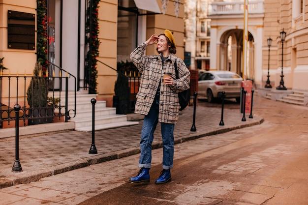 Charmante Femme En Manteau Surdimensionné Avec Sourire Regarde à Distance Photo gratuit