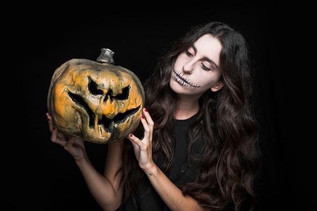 Charmante femme montrant la citrouille d'halloween Photo gratuit
