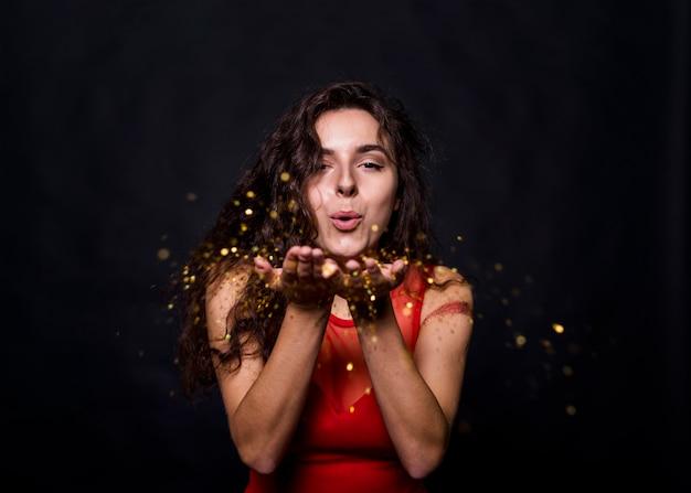 Charmante femme soufflant des paillettes Photo gratuit