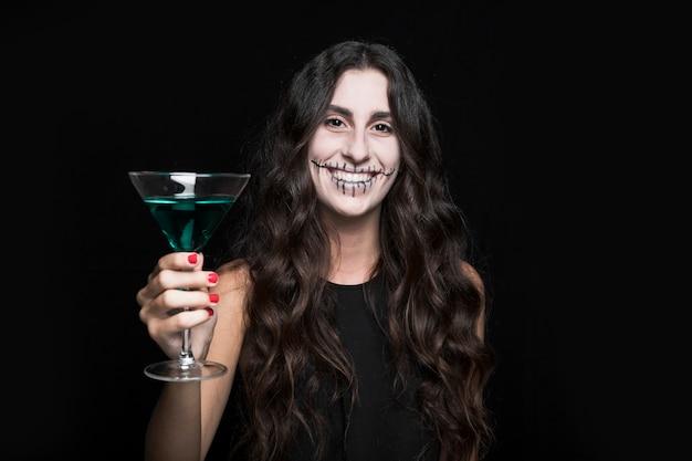 Charmante femme souriante tenant gobelet avec liquide turquoise Photo gratuit
