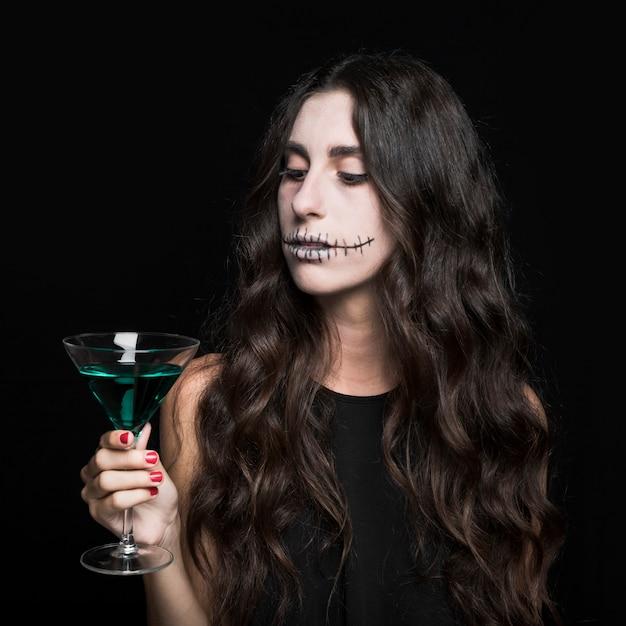 Charmante femme tenant gobelet de liquide turquoise Photo gratuit