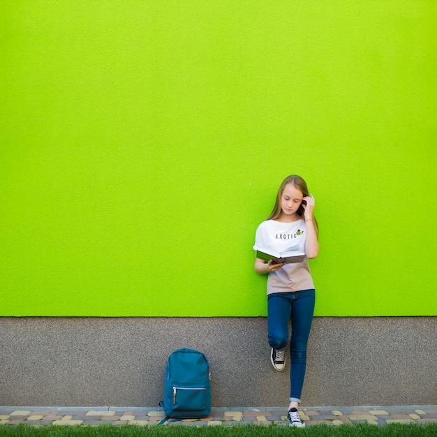 Charmante fille posant avec un manuel Photo gratuit