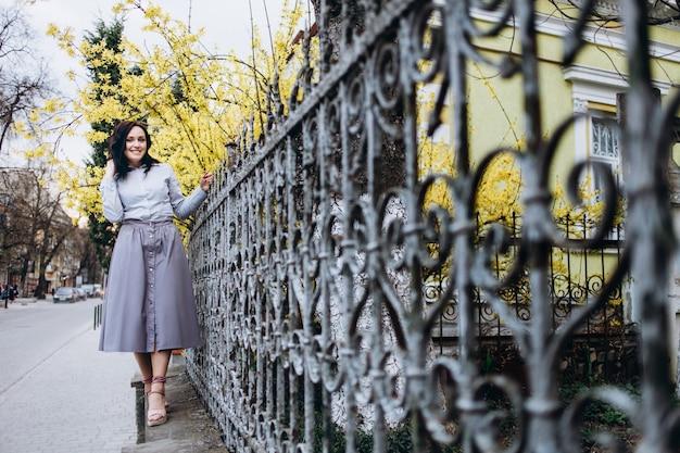 La charmante fille se tient près de la porte Photo gratuit