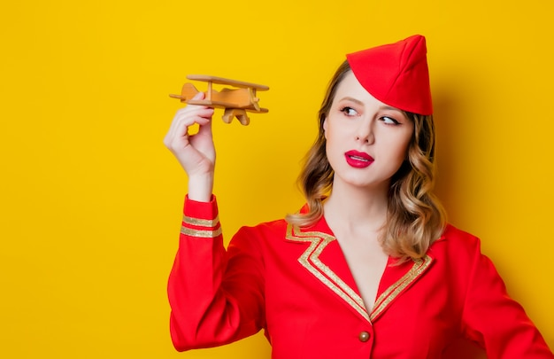 Charmante hôtesse vintage vêtue de l'uniforme rouge avec avion Photo Premium