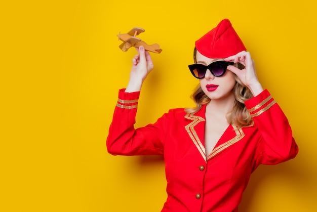 Charmante hôtesse vintage vêtue de l'uniforme rouge avec avion Photo Premium