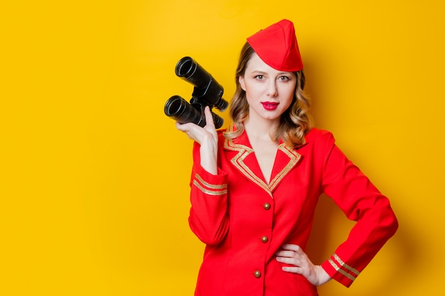 Charmante hôtesse vintage vêtue d'un uniforme rouge avec des jumelles Photo Premium