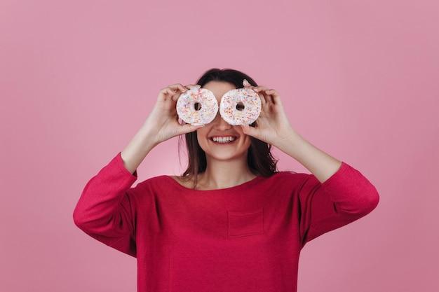 Charmante jeune brune tient des beignets roses devant ses yeux posant dans la chambre rose Photo gratuit