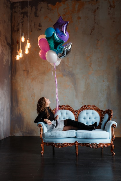 Charmante jeune femme brune tenant un grand paquet de ballons à l'hélium se trouvant sur un canapé Photo gratuit