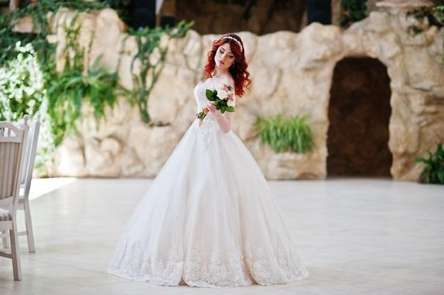 Charmante mariée aux cheveux roux avec bouquet de mariée Photo Premium