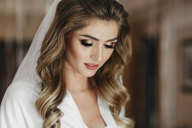Charmante mariée blonde avec des boucles et une peau brillante pose en robe de soie blanche dans la chambre Photo gratuit