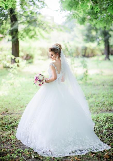 Charmante mariée pose avec bouquet de mariage coloré dans le parc Photo gratuit