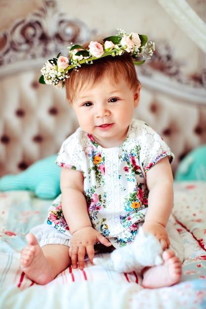 Charmante Petite Fille En Couronne De Roses Assise Sur Des Couvertures Souples Photo gratuit