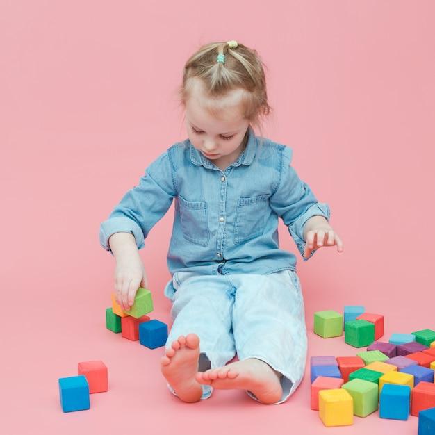 Une Charmante Petite Fille En Jean Sur Fond Rose Joue Avec Des Cubes En Bois Colorés. Photo Premium