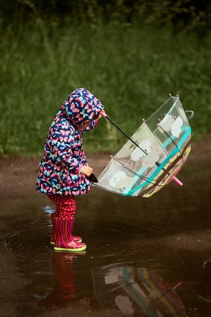 Charmante petite fille avec un parapluie s'amuse debout dans des bottes en caoutchouc dans la piscine après la pluie Photo gratuit