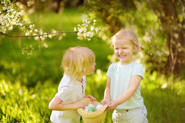 De charmants petits enfants chassent les œufs peints dans le parc du printemps le jour de pâques Photo Premium