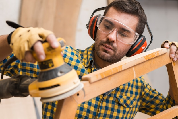 Charpentier adoucissant les bords de meubles en bois avec ponceuse électrique Photo gratuit