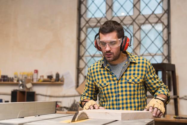 Charpentier ciblé au travail avec une planche de bois Photo gratuit