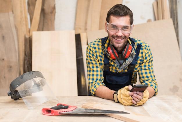 Un charpentier debout derrière le établi à l'aide d'un téléphone portable Photo gratuit