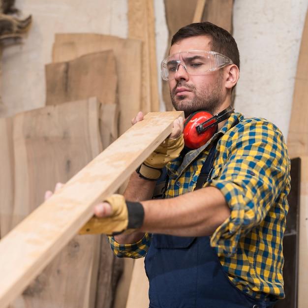 Charpentier, homme, sérieusement, regarder, planche bois Photo gratuit