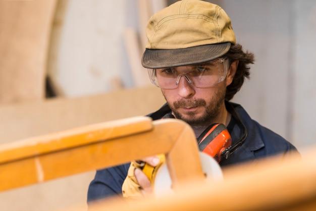 Un charpentier polit des meubles en bois avec une ponceuse dans l'atelier Photo gratuit