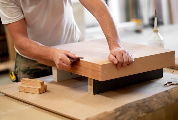 Charpentier ponçant le bord d'un bloc de bois Photo Premium