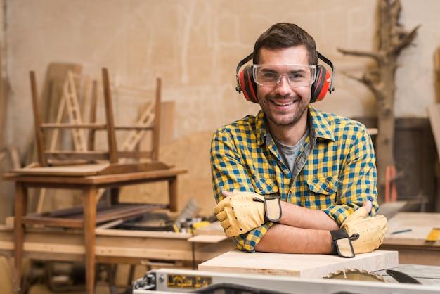 Charpentier, porter, lunettes protectrices, et, oreillette, s'appuyer, table, scie, dans, les, atelier Photo gratuit