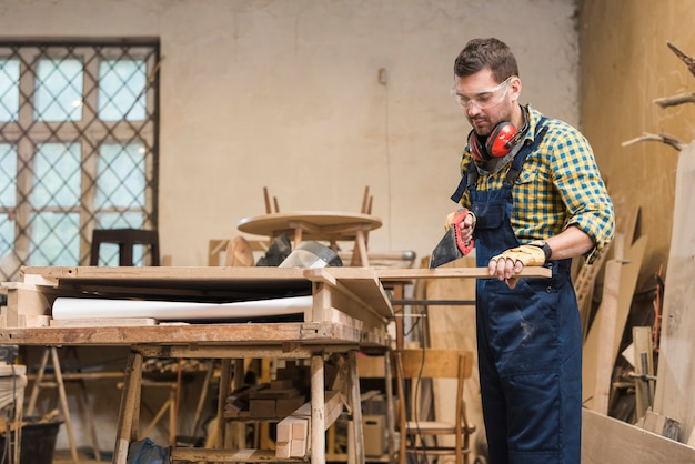 Charpentier professionnel coupant la planche de bois avec la scie à main dans l'atelier Photo gratuit