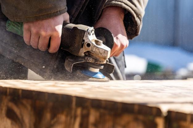 Charpentier travaillant le bois, enlève la vieille peinture Photo Premium