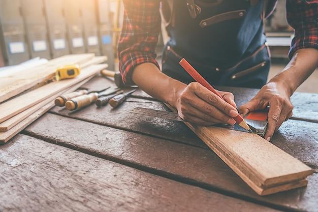 Charpentier travaillant avec de l'équipement sur une table en bois dans un atelier de menuiserie Photo Premium