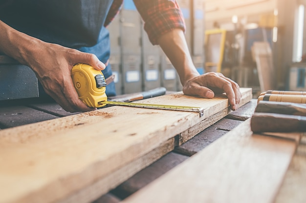 Charpentier travaillant avec des équipements sur une table en bois dans l'atelier de menuiserie. Photo Premium