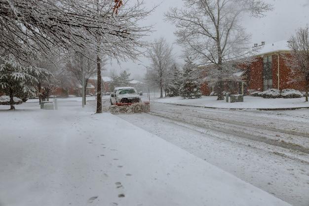 Chasse-neige déneigeant une route urbaine Photo Premium