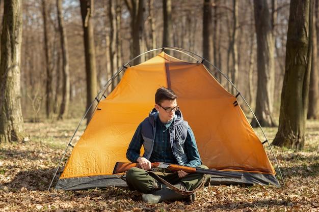Chasseur avec une arme à feu dans la forêt assis près de la tente Photo Premium