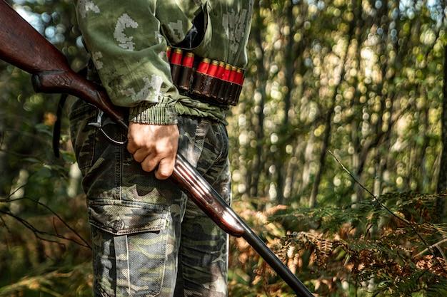 Chasseur avec une arme à la main dans les vêtements de chasse dans la forêt d'automne Photo Premium
