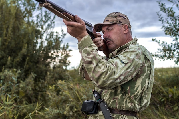 Chasseur en uniforme avec un fusil de chasse. chasse Photo Premium
