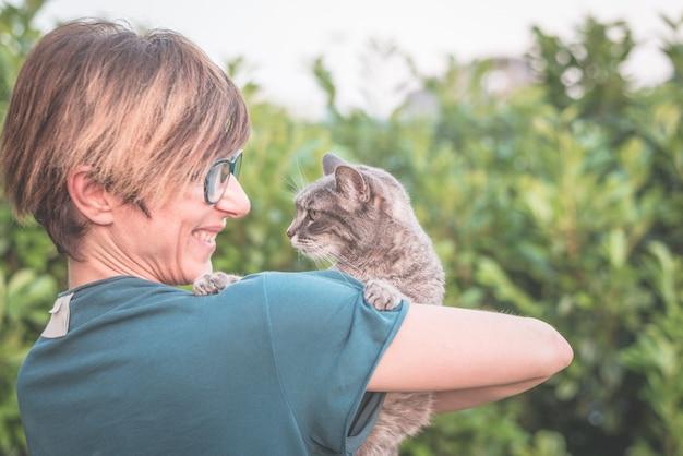 Chat domestique ludique tenu et câlin de femme souriante avec des lunettes Photo Premium