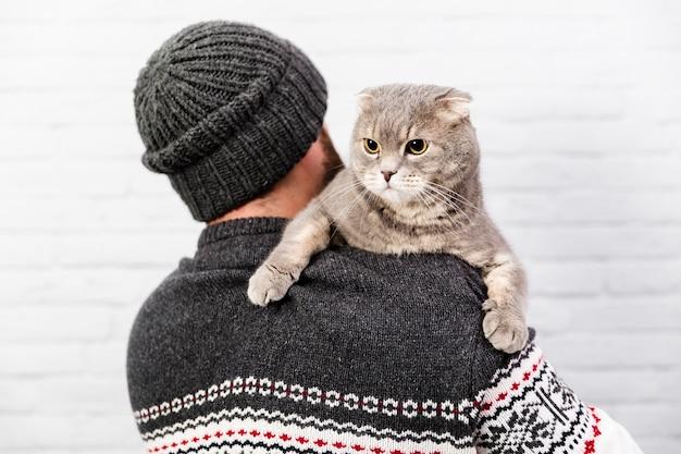 Chat mignon tenu par le propriétaire Photo gratuit