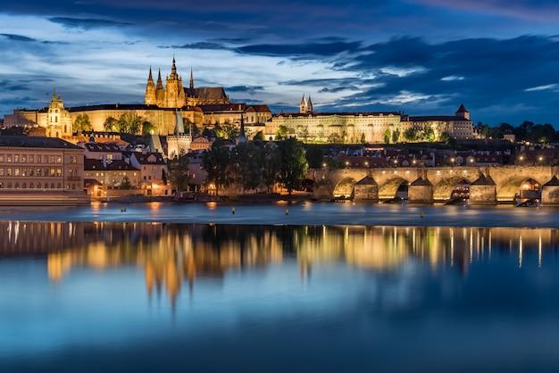Château de prague avec ciel bleu coucher de soleil nuageux et pont charles s'allument Photo Premium