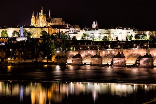 Le château de prague et le pont charles sur la rivière vltava la nuit à prague, en république tchèque Photo Premium