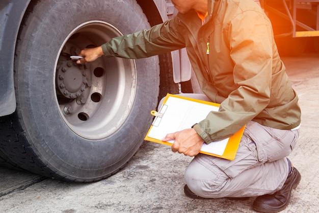 Chauffeur de camion tient un presse-papiers avec l'inspection d'un pneu de camion. Photo Premium