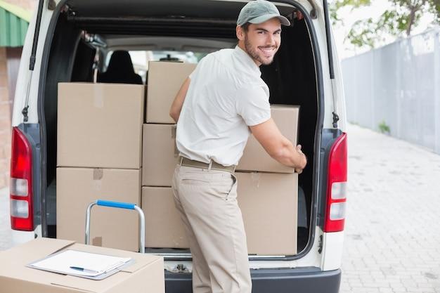 Chauffeur de livraison chargeant sa camionnette avec des boîtes Photo Premium