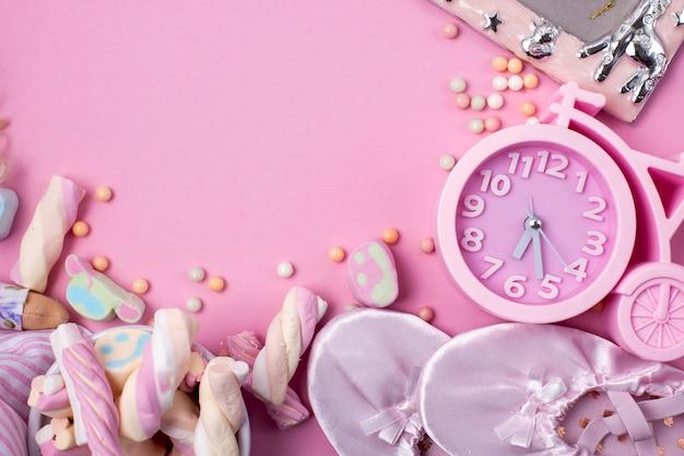 Chaussons de ballet, bonbons et montres sur fond rose. Photo Premium